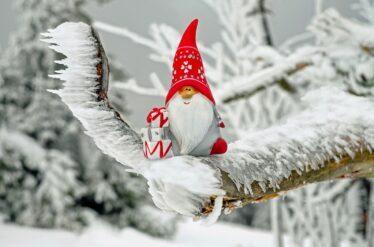 deda mraz sedi sa poklonom na drvetu